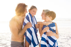 Children after swim. Wet son and daughter draped in towel embracing by parents after swim. Happy family at beach after swim in the tropical sea. Smiling father Royalty Free Stock Photography