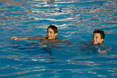 Children swimming. Two teenage boys swimming in a deep blue water, smiling, looking into the camera Stock Photo