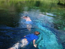 Children Swimming. Two children exploring the shallow waters of a small spring in Florida.  Water drops on the lens give the picture a very surreal appearance Stock Photography