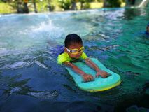 Children swimming. Boy Practice Swimming. Activities on the pool. Playing in water, happiness and holiday royalty free stock image