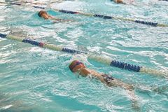 Children swimming freestyle at swimming lesson stock photos