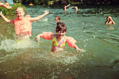Children. Swimming in the lake and sprinkles Stock Photos