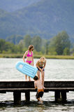 Children swimming off a pier. Portrait of three children playing in water Royalty Free Stock Photos