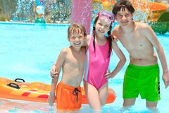Children in swimming pool. Three siblings standing in swimming pool with scuba diving mask and a floating air mattress in Egypt Stock Image
