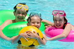 Children in swimming pool. Three children in swimming pool with scuba diving masks and snorkels floating with an air mattress in Egypt Stock Photos