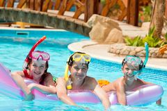 Children in swimming pool. Three children in swimming pool with scuba diving masks and snorkels floating with an air mattress in Egypt Stock Photo