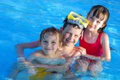 Children in swimming pool. A view of three children posing together while in the water of a refreshing swimming pool Stock Photography