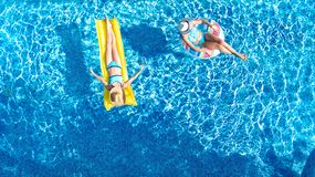 Children in swimming pool aerial drone view fom above, happy kids swim on inflatable ring donut and mattress, girls have fun. Children in swimming pool aerial stock photos