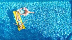 Children in swimming pool aerial drone view fom above, happy kids swim on inflatable ring donut and mattress, girls have fun. Children in swimming pool aerial royalty free stock photo