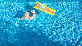 Children in swimming pool aerial drone view fom above, happy kids swim on inflatable ring donut and mattress, girls have fun. Children in swimming pool aerial stock image