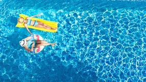 Children in swimming pool aerial drone view fom above, happy kids swim on inflatable ring donut and mattress. Active girls have fun in water on family vacation stock image