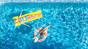 Children in swimming pool aerial drone view fom above, happy kids swim on inflatable ring donut and mattress. Active girls have fun in water on family vacation stock images