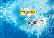 Children in swimming pool aerial drone view fom above, happy kids swim on inflatable ring donut and mattress. Active girls have fun in water on family vacation royalty free stock photos