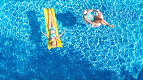 Children in swimming pool aerial drone view fom above, happy kids swim on inflatable ring donut and mattress, girls have fun. Children in swimming pool aerial royalty free stock image