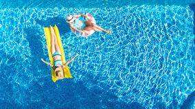Children in swimming pool aerial drone view fom above, happy kids swim on inflatable ring donut and mattress, girls have fun. Children in swimming pool aerial stock photo