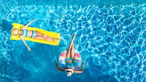 Children in swimming pool aerial drone view fom above, happy kids swim on inflatable ring donut and mattress, girls have fun. Children in swimming pool aerial royalty free stock photos