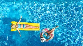 Children in swimming pool aerial drone view fom above, happy kids swim on inflatable ring donut and mattress, girls have fun. Children in swimming pool aerial stock photography