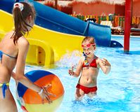 Children swimming in pool. Little girl playing ball in swimming pool royalty free stock images