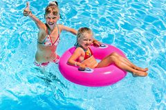 Children  in swimming pool. Children sitting on inflatable ring in swimming pool Stock Photos