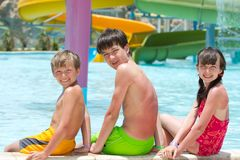 Children with Swimming Pool Slide. Smiling children sitting on the edge of a resort's swimming pool Royalty Free Stock Photos