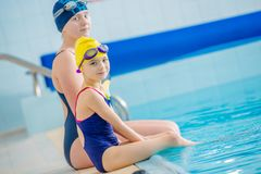 Children and Swimming Pool. Two Young Caucasian Girls Seating on the Edge of the Large Public Swimming Pool Stock Photography