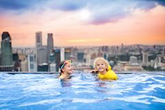Kids swim in Singapore roof top swimming pool. Children swimming in roof top outdoor pool on family vacation in Singapore. City skyline from infinity pool in Stock Photos