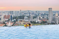 Kids swim in Singapore roof top swimming pool. Children swimming in roof top outdoor pool on family vacation in Singapore. City skyline from infinity pool in Stock Images