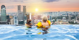 Kids swim in Singapore roof top swimming pool. Children swimming in roof top outdoor pool on family vacation in Singapore. City skyline from infinity pool in Stock Photography
