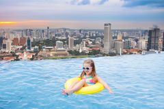 Kids swim in Singapore roof top swimming pool. Children swimming in roof top outdoor pool on family vacation in Singapore. City skyline from infinity pool in Royalty Free Stock Photo