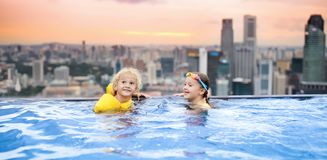 Kids swim in Singapore roof top swimming pool. Children swimming in roof top outdoor pool on family vacation in Singapore. City skyline from infinity pool in Stock Image