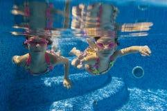 Children swimming underwater in pool Stock Photos