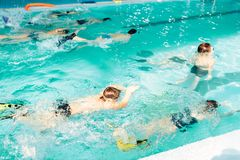 Children swimming underwater in pool. Kids diving with colorful flippers and goggles in clean blue water. Happy kids in modern sport center. Concept of fun Royalty Free Stock Image