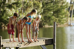 Children In Swimwear Standing On Jetty By Lake Stock Image
