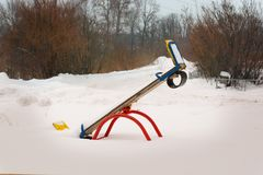 Children swing in the snow on the street. Against a backdrop of bushes Royalty Free Stock Images