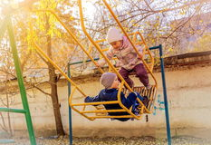 Children in the swing. Children swinging on a swing in the yard Stock Images