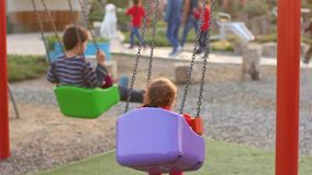 Children on a Swing. Two children ride on a swing. Autumn season stock video footage
