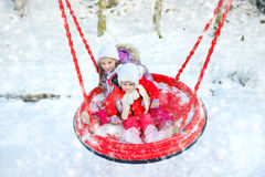 Children on a swing in winter park Royalty Free Stock Photography