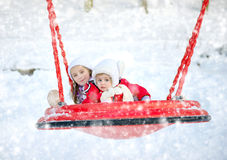 Children on a swing in winter park Royalty Free Stock Images