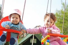 Children swinging. Sister and little brother swinging Stock Photography