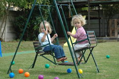 Children on swing. Two full bodies of beautiful little caucasian white blond girls with cute expression in their faces sitting on a double swing, swinging Royalty Free Stock Images
