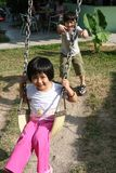 Children swinging. Happy children playing swing at the playground in the park on sunny day Stock Images