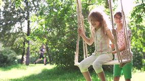 Children swinging on a swing in summer Park. two little sisters playing in the fresh air. the older sister shakes her. Little girl swinging on a swing in summer stock video