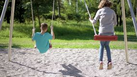 Children on swings at playground. Happy two children ride on a swing at summer park. Cute teen boy and girl swings at playground outdoors stock video footage