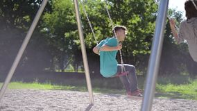 Children on swings at playground. Happy two children ride on a swing at summer park. Cute teen boy and girl swings at playground outdoors stock video