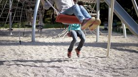 Children on swings at playground. Happy two children ride on a swing at summer park. Cute teen boy and girl swings at playground outdoors stock footage