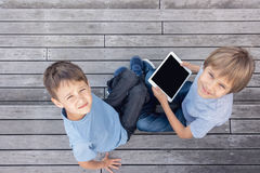Children with tablet computers outdoor. People education learning technology leisure concept. Children playing with tablet computers outdoors. Education learning Royalty Free Stock Images