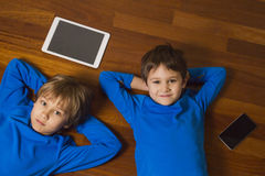 Children with tablet pc, mobile phone lying on wooden floor. Top view. Education, learning, technology concept Royalty Free Stock Images