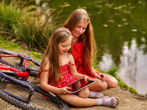 Children with tablet pc near bicycle into river in park . Bikes cycling girl. Girl wearing red polka dots dress recreation near bicycle into park. Children royalty free stock image