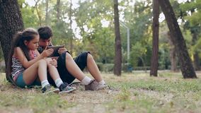Children with tablet pc outdoors. Girl and boy on grass with computer. A boy and a girl with the tablet on the nature. Boy with headphones. Brother and sister stock video