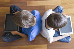 Children with tablets PC sitting on wooden floor at home. Top view. Education, learning, technology, friends, school Stock Photos